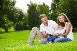 Mother, father and small son have a rest on lawn in summer park