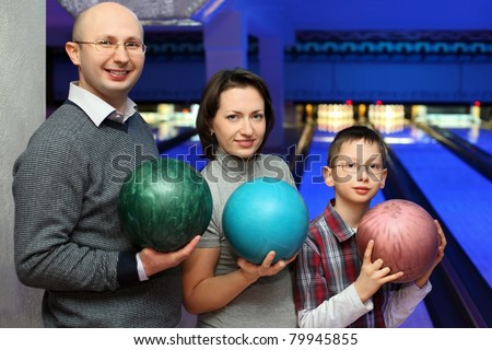 Mother, father and son, stand alongside and hold balls for bowling, focus on son