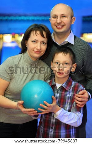 Mother, father and son, stand alongside and hold one ball for bowling