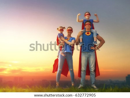 Mother, father and their daughters are playing outdoors. Mommy, daddy and children girls in an Superhero's costumes. Concept of super family. #632772905