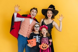 Mother, father and their kids having fun at party. Happy family celebrating Halloween. People wearing carnival costumes and makeup on yellow wall background.
