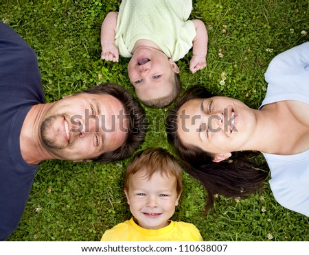 mother, father, son and daughter having fun on the grass