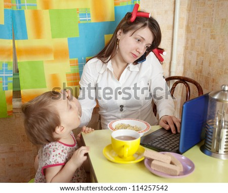 Mother feeding baby and  using  latop at kitchen in morning
