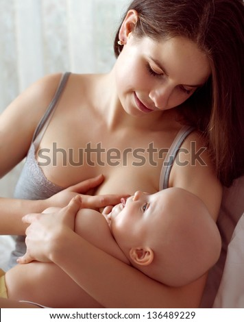 mother feeding breast her baby in the bed