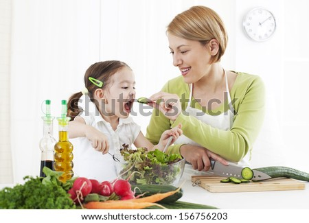 Mother feeding child, while chopping vegetable - stock photo