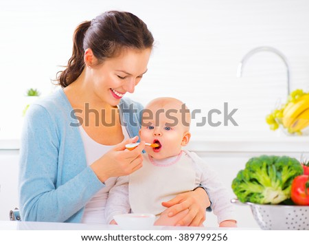 Mother Feeding Her Baby Girl with a Spoon. Mother Giving Food to her adorable Child at Home. Baby food