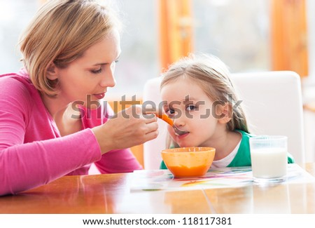 Mother feeding her daughter by spoon