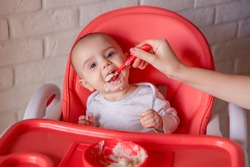 Mother feeding her happy baby  with spoon .mother's hand feeds the baby porridge at home . The baby is sitting on a high chair and eating porridge. the first solid foods.