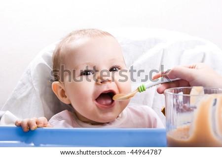 Shutterstock Mother feeding her happy little cute daughter