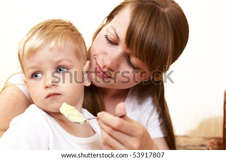 mother feeding her little son at home