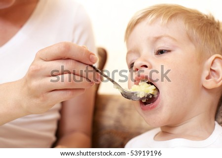 mother feeding her little son at home - stock photo