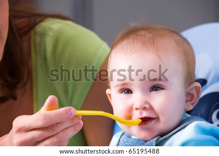 Mother feeding hungry baby in the highchair in kitchen