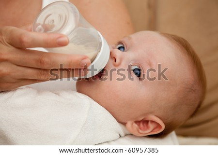 Mother feeding newborn son with feeding bottle
