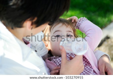 Mother feeding one year baby girl with feeding bottle in the street