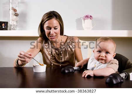 Mother feeding six month old baby sitting in high chair