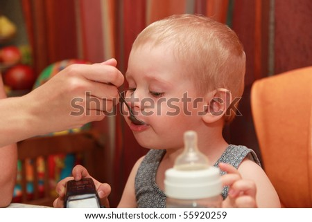 Mother feeding the child from a spoon - stock photo