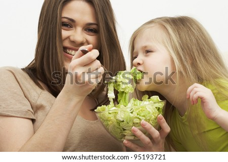 Mother feeds little girl with organic green food #95193721