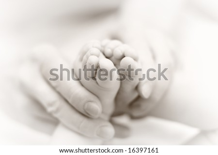 Mother gently hold baby leg in hand. Slightly toned black & white image with soft focus on babie's foot