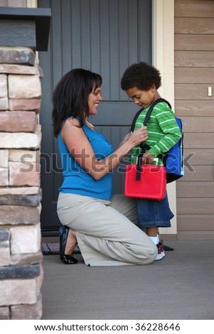 Mother gets child ready for first day of school