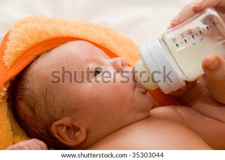 Mother give drink her baby boy by feeding bottle - stock photo