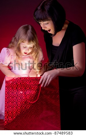 Mother give gift to her little daughter