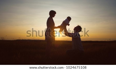 Stock Photo Mother gives baby to her father in arms against beautiful sunset