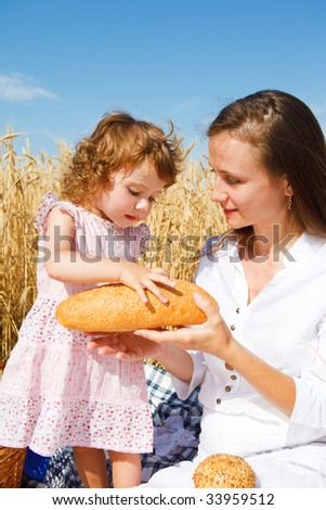 Mother giving a  bread loaf to her daughter