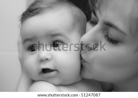 black and white kissing photography. stock photo : Mother giving a