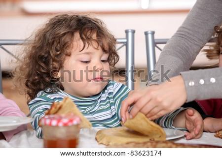 Mother giving children breakfast