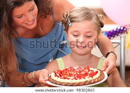 Mother giving daughter cake