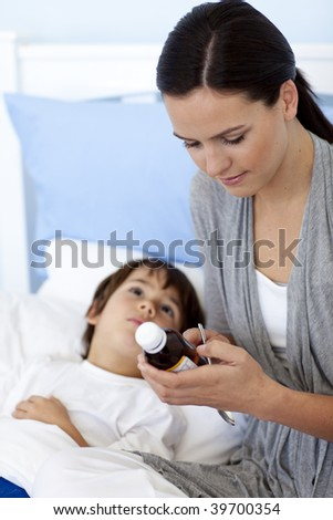 Mother giving her son syrup because of the flu
