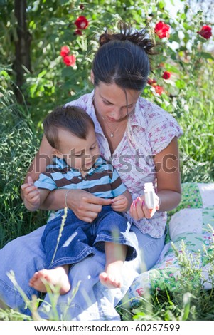 Mother giving homeopathic medicine to her son. Shallow DOF, main focus on their hands switching the tablet.