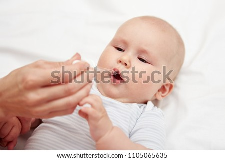 Mother giving liquid medicine to her baby. Healthcare and child treatment concept.