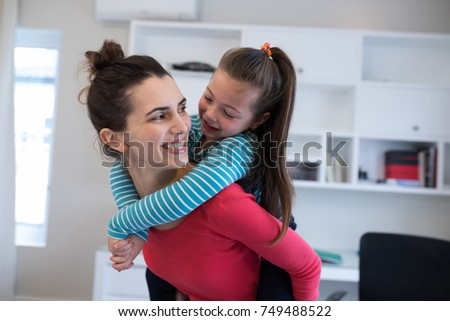 Mother giving piggyback to daughter at home. Social distancing and self isolation in quarantine lockdown for Coronavirus Covid19