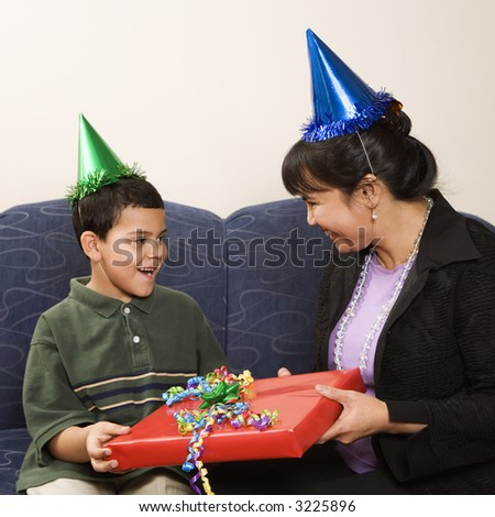 Mother giving present to surprised son at birthday party.