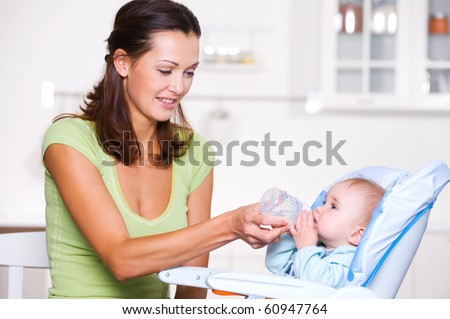 Mother giving the water to  baby  in the highchair in kitchen