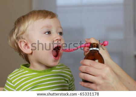 Mother giving 2 years old baby boy medicine, cough syrup on a spoon. Sick child.