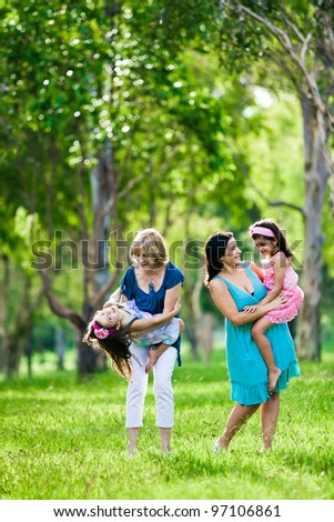 Mother, grandmother and daughters having laugh in the park