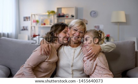 Mother granny and girl hugging, sitting on sofa at home, family closeness, love