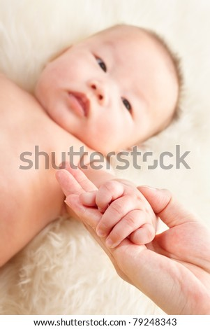 mother hand holding her baby boy's hand