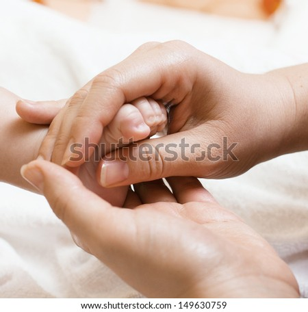 Mother hand massaging baby feet. - stock photo