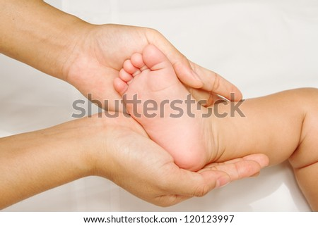 Mother hand massaging foot of her baby on white background