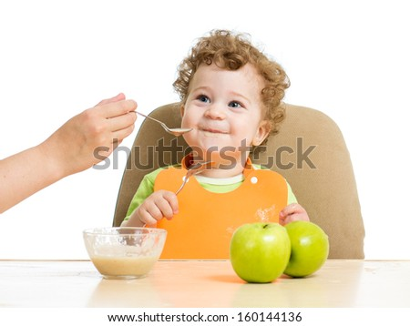 mother hand spoon feeding baby boy