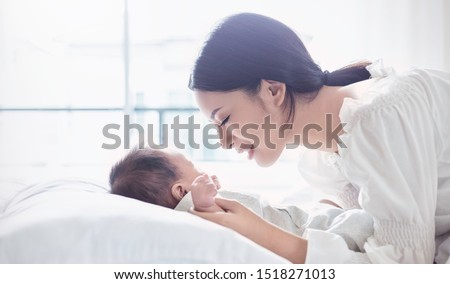 Mother hands holding newborn baby feet. Close up portrait of beautiful young asian mother with her newborn baby. Healthcare and medical love lifestyle mother's day concept