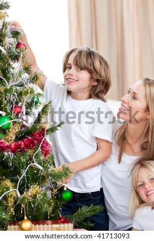 Mother hanging Christmas decorations with her children in the living-room