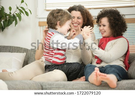 Mother having fun with daughter and son on sofa