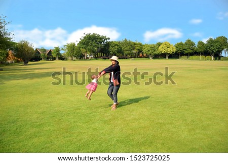 Mother held her baby's hand and swirled happily on the lawn of the garden, with the sky in the background. #1523725025