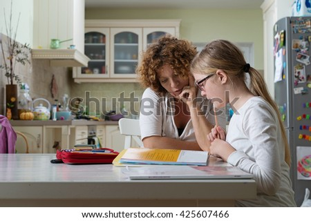 Mother helping daughter with her homework at the table in the dining room.