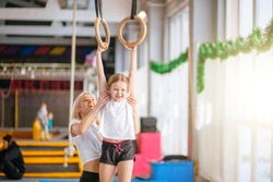 Mother helping her daughter to play sports on gymnastic rings