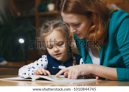 Mother helping kid after school. preschooler doing homework with help of tutor. home teaching concept.